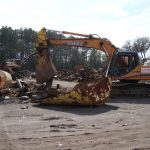 Shear crane cutting junk metal in the scrap yard