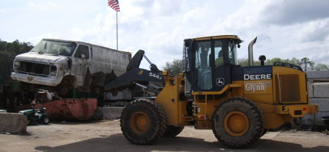 Image of Glynn Iron bulldozier moving a junk van